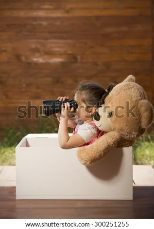 Beautiful little girl with binoculars inside white wooden box with toy bear exploring surroundings pretending to be on safari - stock photo