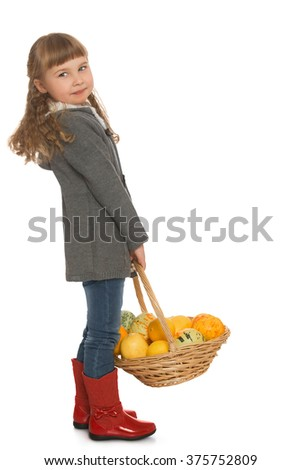 Beautiful little girl with blond hair and short bangs, in autumn clothes and red boots. A girl holding a basket in which is autumn harvest - Isolated on white background - stock photo