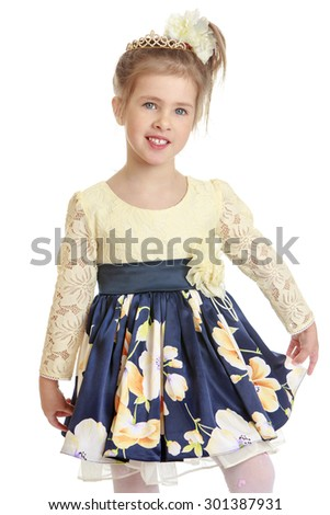 Beautiful little girl with blond hair braided in that big white bow. On the girl wearing elegant dress luxuriant. Close-up-Isolated on white background - stock photo