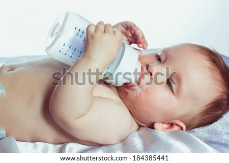 beautiful little girl with blue eyes lying on her back in diapers and holding a bottle of milk - stock photo