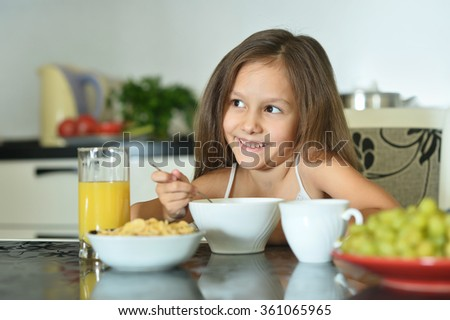 Beautiful little girl with breakfast - stock photo