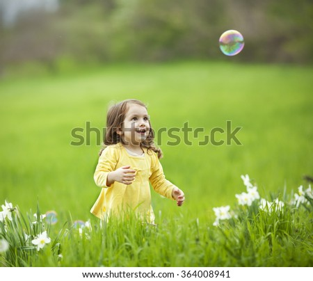 Beautiful little girl with bubble in the park
