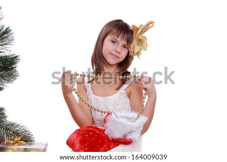 Beautiful little girl with Christmas tree and gifts over white on Holiday theme/Beautiful caucasian little girl with golden flower on her hair over Christmas decoration