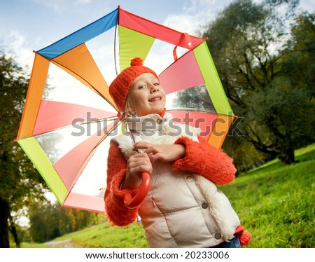 Beautiful little girl with colorful umbrella - stock photo