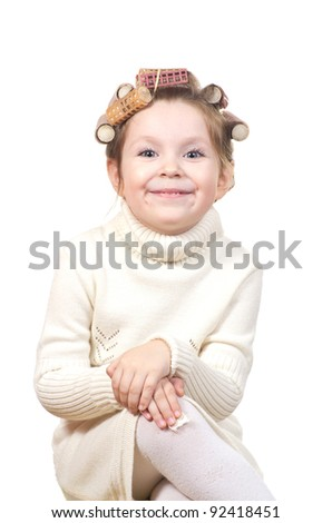 Beautiful little girl with curlers on her head. Isolated on white background.