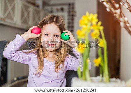 Beautiful little girl with easter eggs. Cozy home atmosphere  - stock photo