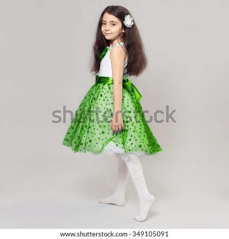 beautiful little girl with flower in her hair.pretty little princess child in green skirt - stock photo