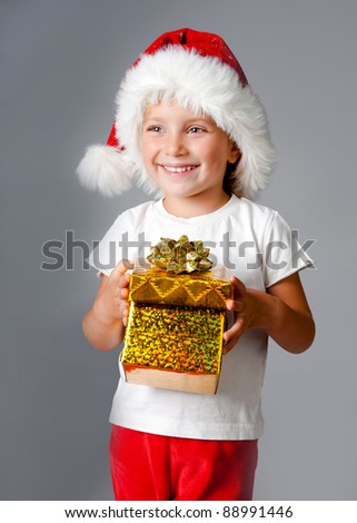 beautiful little girl with gifts in santa hat - stock photo