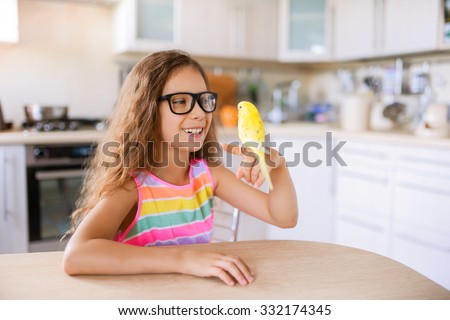 Beautiful little girl with glasses holding the finger yellow wavy parrot.
