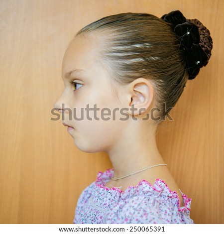 Beautiful little girl with hair in beam profile on background of wooden wall. - stock photo