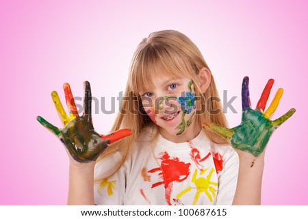 Beautiful little girl with hands painted in colorful paints over pink background - stock photo