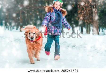 beautiful little girl with her dog on the snow in winter - stock photo