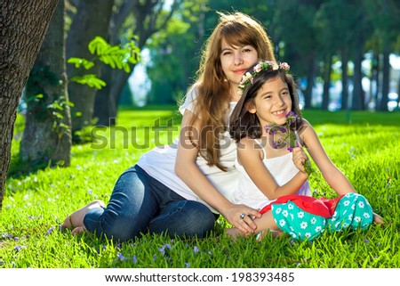 Beautiful little girl with her young mother sitting close together on lush green spring grass in a wooded garden smiling at the camera