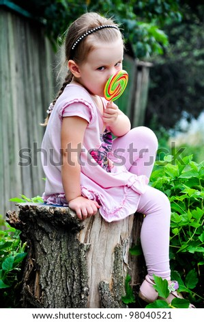 Beautiful little girl with lollipop sits on the stump - stock photo