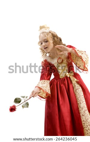 Beautiful little girl with long blonde hair in the princess costume using a red rose like a magic wand at the white background. Red and gold empire dress - stock photo