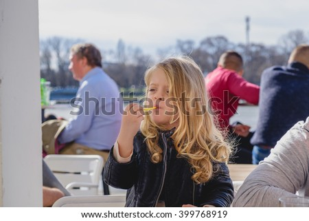 Beautiful little girl with long blonde hair looking away while eating outdoor