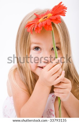 Beautiful little girl with long blonde hairand red flower - stock photo