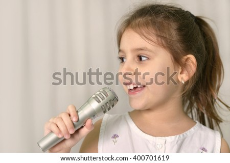 Beautiful little girl with microphone - stock photo