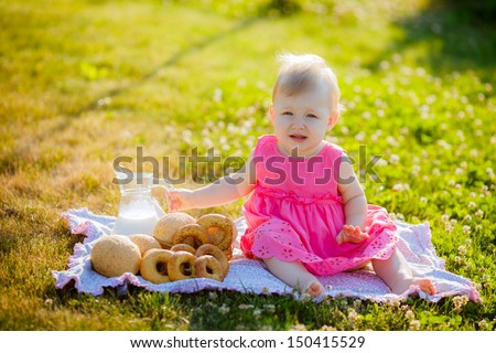 beautiful little girl with milk and buns outdoors - stock photo