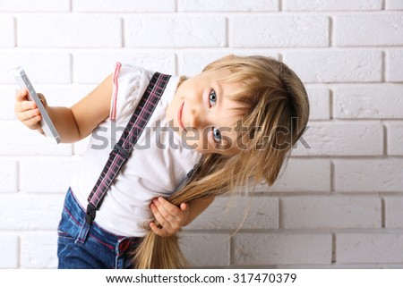 Beautiful little girl with mobile phone on light wall background - stock photo