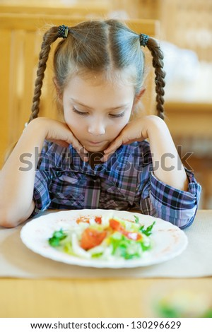 Beautiful little girl with pigtails sitting on table in restaurant and looks at prepared dish. - stock photo
