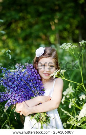 Beautiful little girl with purple lupines outdoors - stock photo