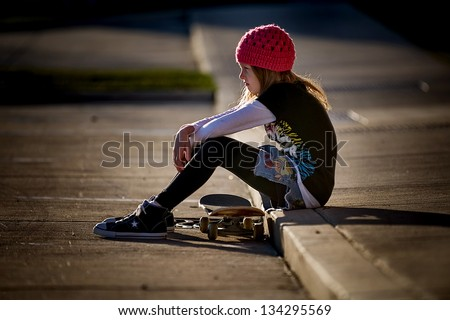 Beautiful little girl with serious face wearing pink knit hat and sitting on curb with her skateboard, looking off into the distance - stock photo