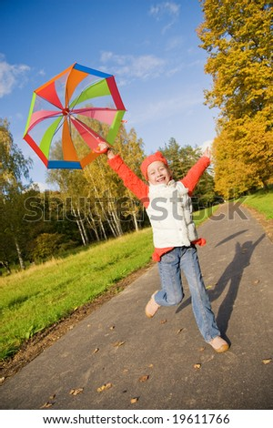 Beautiful little girl with umbrella in a forest - stock photo