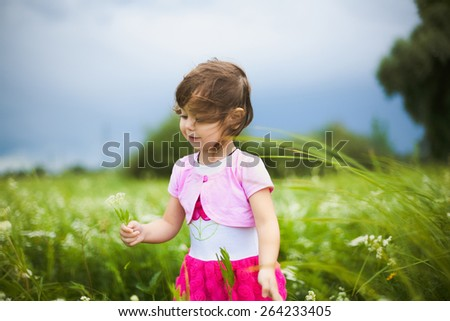 beautiful little girl with wild flowers in green meadow. funny cheerful child playing outdoors.  - stock photo