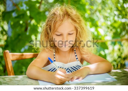Beautiful little girl writes pen in exercise book. - stock photo