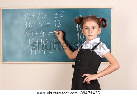 beautiful little girl writing on classroom board - stock photo