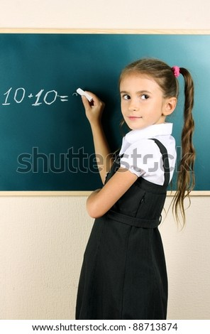 beautiful little girl writing on classroom board