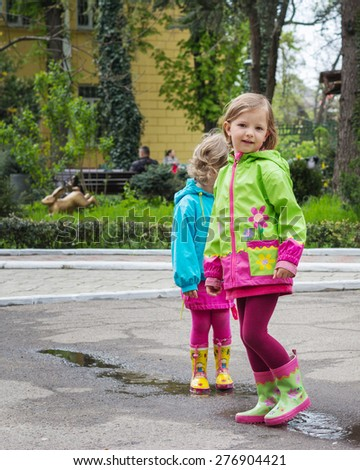 Beautiful little girls in the Park after the rain. Selective focus.