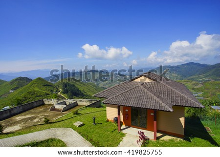 Beautiful little house on top of the hill with lovely blues sky and dramatic cloud formation - stock photo