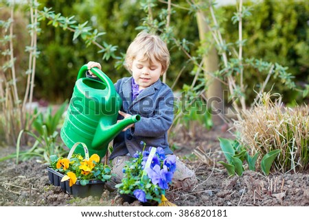 beautiful little kid boy helping with gardening in spring garden funny child planting flowers