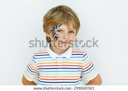 Beautiful little kid boy with face painted with a spider web, on a birthday or halloween party. happy child having fun. - stock photo