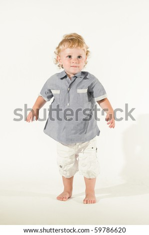 Beautiful little kid standing in equilibrium for his first steps isolated on white background, little sepia toning - stock photo