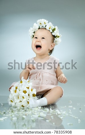 beautiful  little kid with  bouquet and diadem of flowers , sit and  smile - stock photo