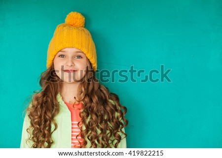 Beautiful little lady in yellow woolen cap against turquoise background - stock photo
