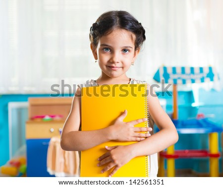 Beautiful little latin girl portrait with book in daycare - stock photo