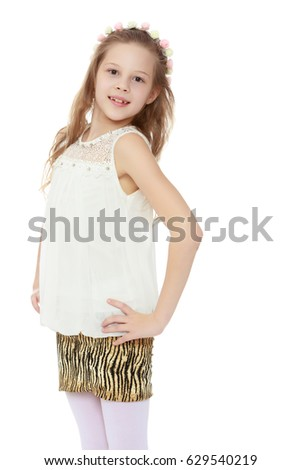 Beautiful little long-haired Caucasian girl posing in Studio.Girl standing with hands on hips.Isolated on white background.