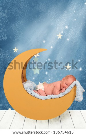 Beautiful Little Newborn baby boy in moon prop - stock photo