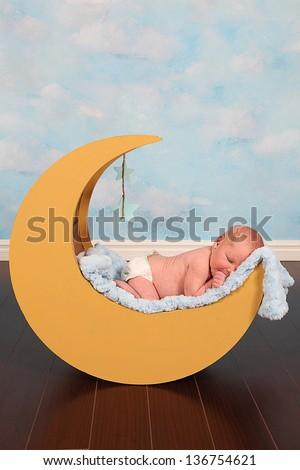 Beautiful Little Newborn baby boy in moon prop - stock photo