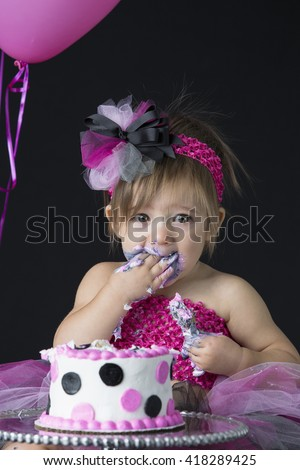 Beautiful little one year old girl messy with birthday cake - stock photo