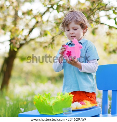 Beautiful little preschoool boy playinig with colorful eggs and having fun outdoors. Square format. - stock photo