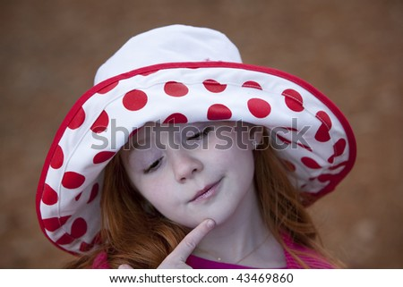 Beautiful little redheaded girl outdoors in red and white hat with pensive look