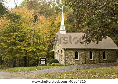 Beautiful little rock country church with white steeple in the Fall season - stock photo