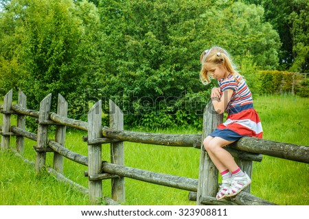 Beautiful little sad girl sitting on wooden fence in countryside. - stock photo