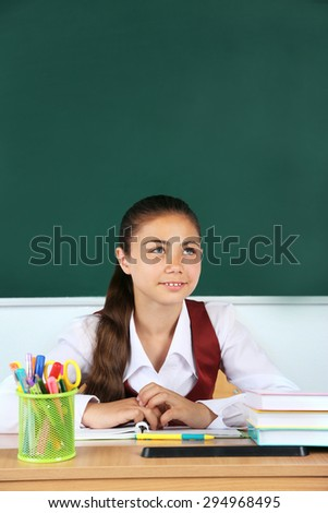 Beautiful little schoolgirl in classroom near blackboard