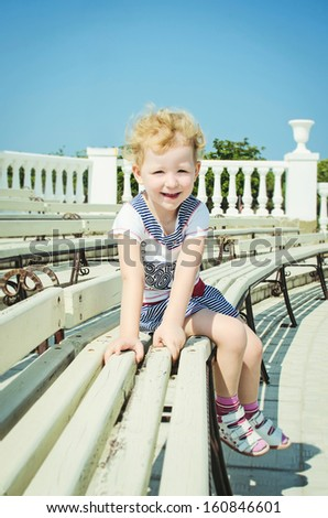 beautiful little smiling girl preschooler sitting on the wooden bench in summer park. Adorable blond child posing outdoors. Sweet trendy girl fashion shot - stock photo